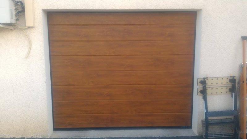 Porte de garage sectionnelle motorisée ton bois. Confort et Patrimoine